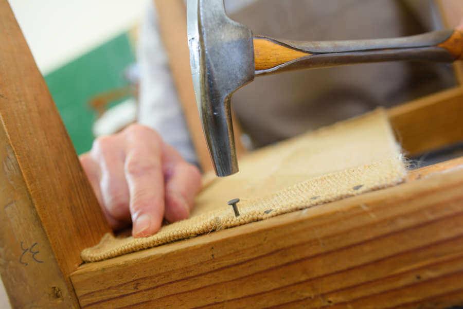 Clavar tejido en madera con clavo y martillo
