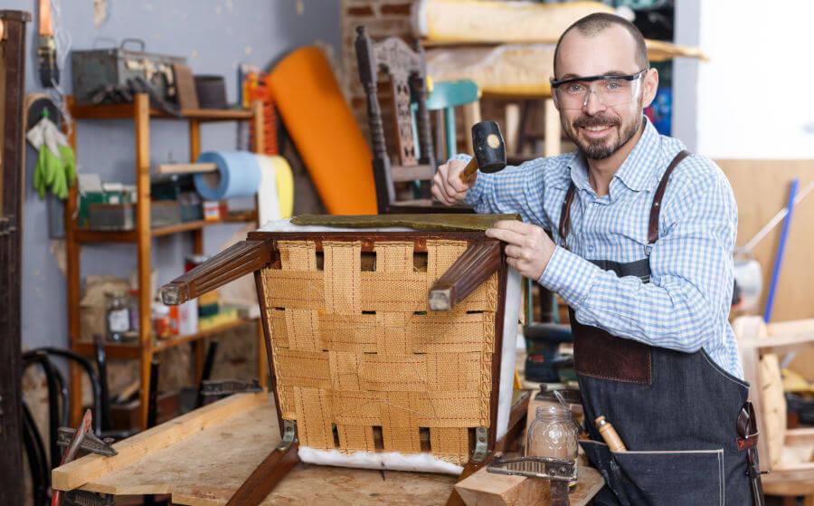 Tensado de las cinchas de una silla en un taller de tapicería