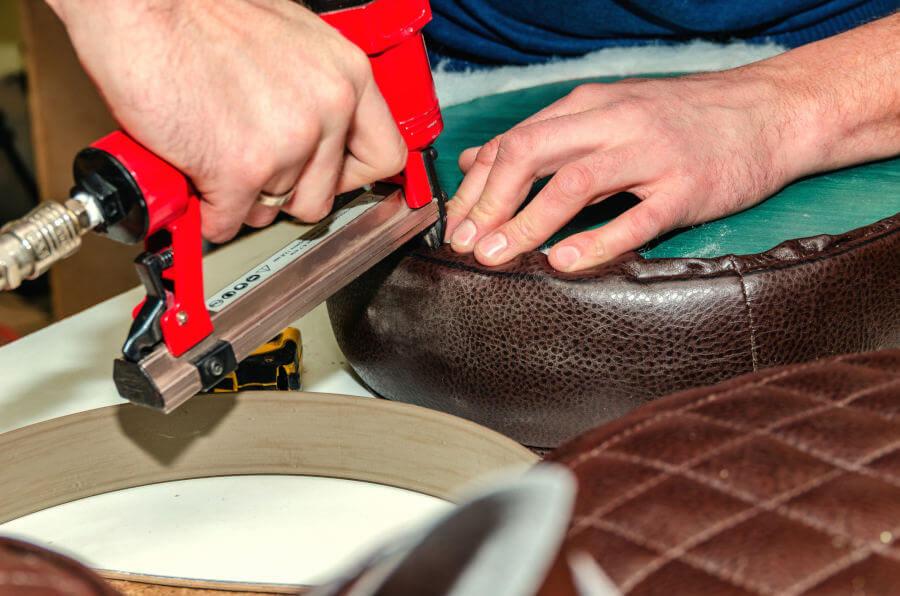 Taller de tapizado: grapadora neumática y asiento de un taburete